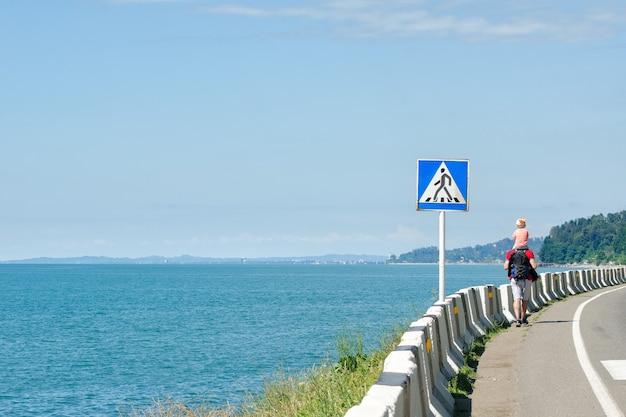 L'homme avec son fils sur les épaules marche le long de la route contre le mur de la mer. panneau de passage pour piétons