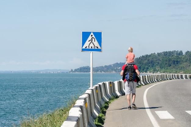 L'homme avec son fils sur leurs épaules marche le long de la route contre le mur de la mer. panneau de passage pour piétons