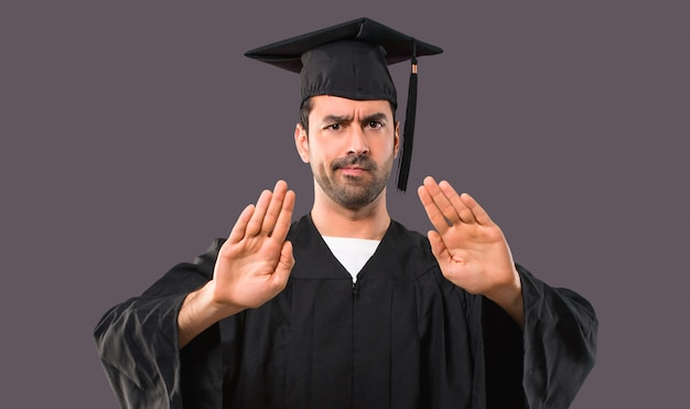 Homme sur son jour de remise des diplômes université faisant stop geste avec sa main pour déçu