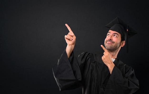 Homme sur son jour de remise des diplômes université montrant avec l'index une bonne idée et looki