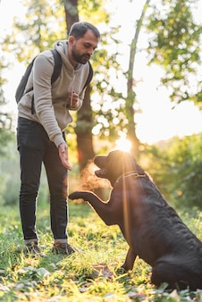 Homme avec son labrador noir jouant dans un parc