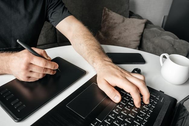 Homme sur son lieu de travail avec ordinateur portable et tablette graphique