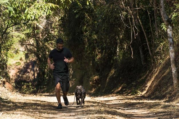 L'homme et son pitbull chien courant sur le chemin de terre lui et le pitbull faisant de l'exercice
