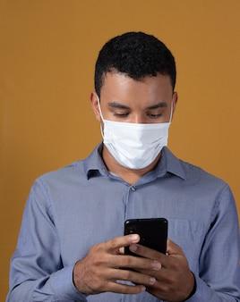 Homme avec son téléphone portable portant un masque