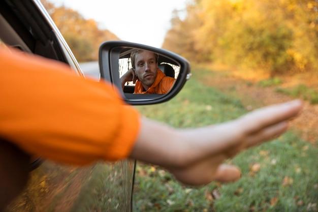 L'homme sort sa main de la voiture lors d'un voyage sur la route