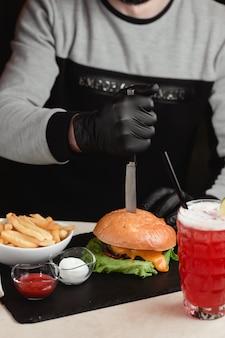 Homme sortant un couteau du hamburger.
