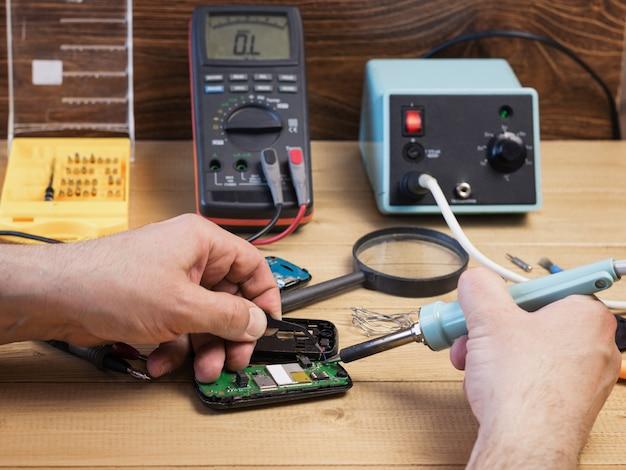 Homme souder des composants électriques dans le téléphone mobile.