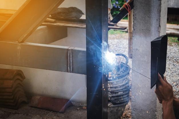 Homme soudeur faisant une structure d'escalier métallique dans un immeuble résidentiel à l'aide d'une machine à souder.