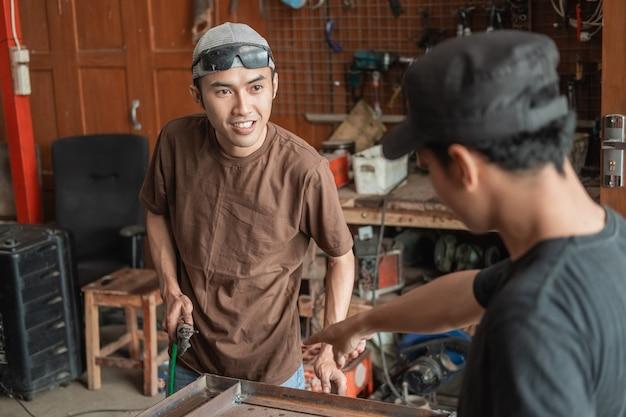 Homme soudeur sourit tout en discutant avec un homme à l'atelier de soudage