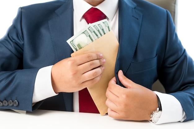 Homme soudoyé conceptuel en gros plan mettant de l'argent dans la poche du costume