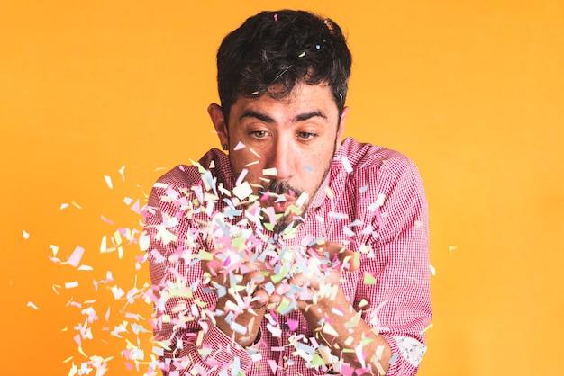 Homme soufflant des confettis sur fond orange
