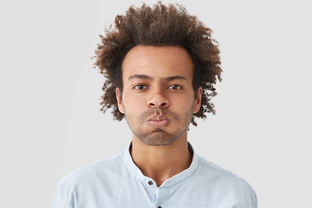 L'homme souffle sur les joues, a une expression de mécontentement, n'est pas satisfait de quelque chose