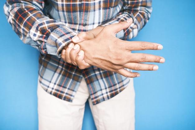 Homme souffrant de douleur dans la main en se tenant debout contre la surface bleue