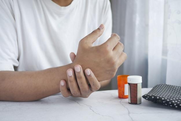 Homme souffrant de douleur à la main et de pilules médicales sur la table