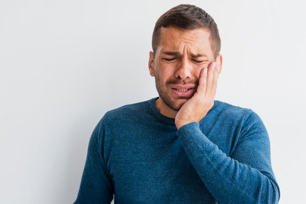 Homme souffrant de douleur tenant une main sur le visage