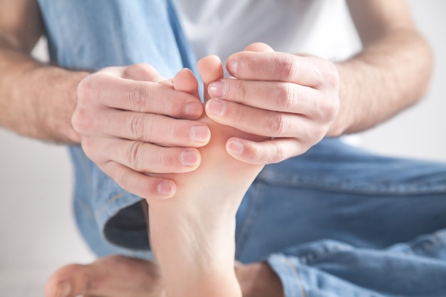 Homme souffrant de douleurs au pied.