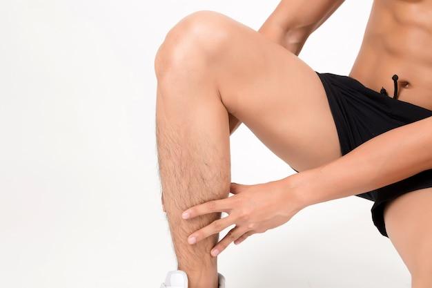 Homme souffrant de douleurs dans les jambes. studio tourné sur fond blanc