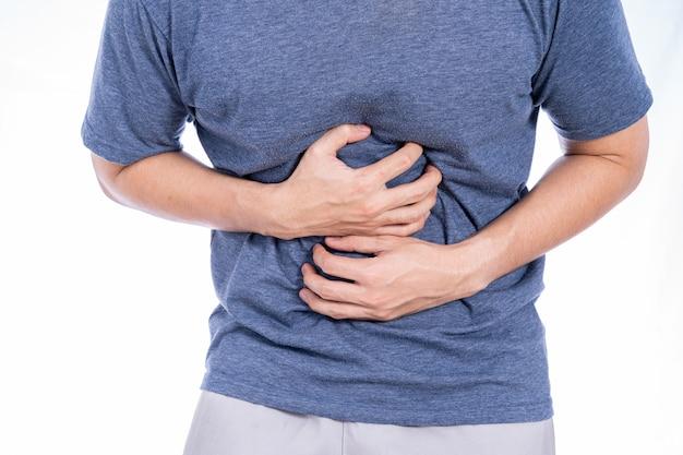 Homme souffrant de douleurs à l'estomac et de blessures fond blanc isolé