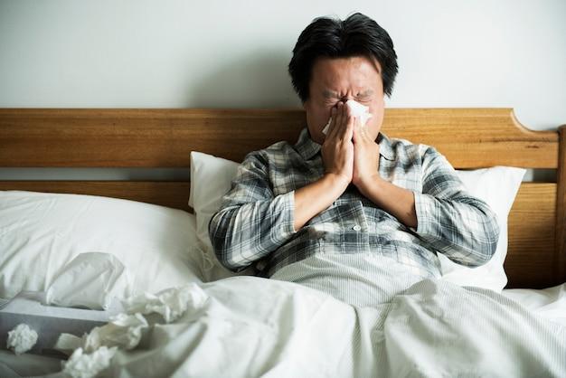 Un homme souffrant de la grippe assis dans son lit
