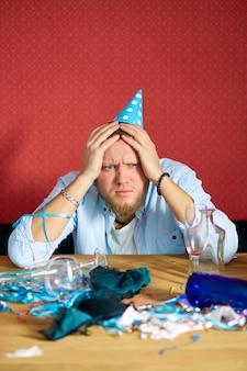 Homme souffrant de gueule de bois à table avec bonnet bleu dans la salle en désordre après la fête d'anniversaire, femme fatiguée après la fête à la maison