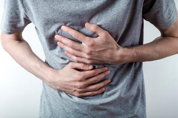 Un homme souffre de reflux acide dans sa poitrine. brûlures d'estomac