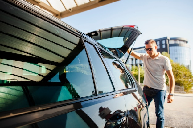 Homme soulevant la porte du coffre d'une voiture noire