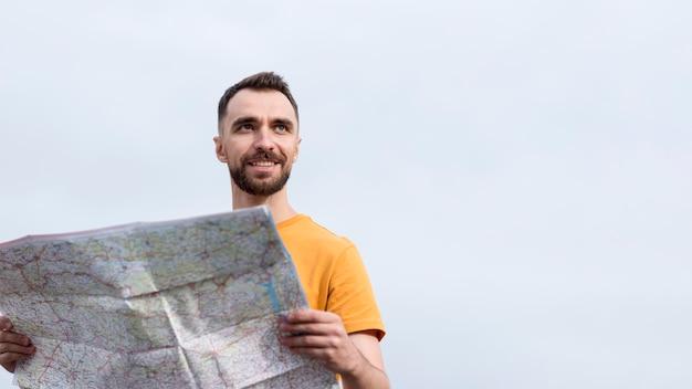 Homme souriant à l'aide d'une carte vue basse