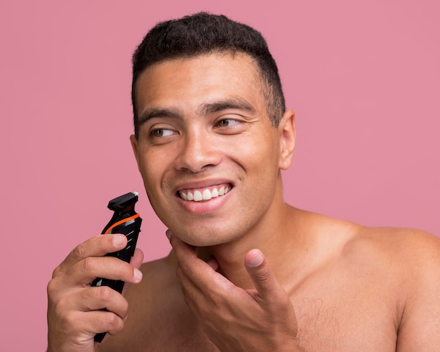 Homme souriant à l'aide d'un rasoir électrique