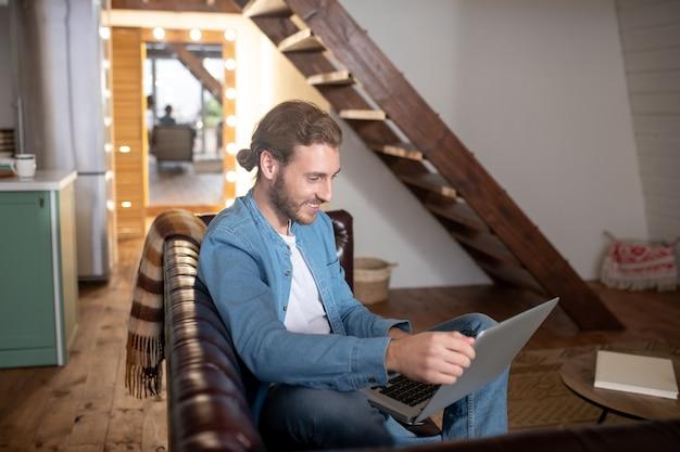 Un homme souriant à l'aide de son ordinateur portable à la maison