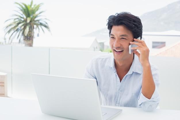 Homme souriant à l'aide de son ordinateur portable et de parler au téléphone