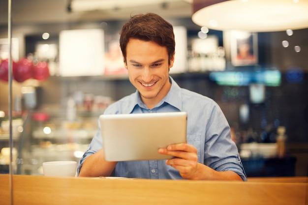 Homme souriant à l'aide de tablette numérique au café