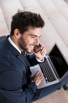 Homme souriant à angle élevé parlant au téléphone