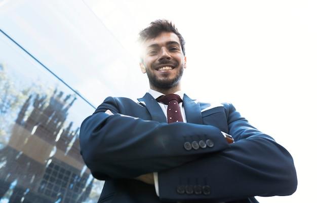 Homme souriant à angle faible en regardant la caméra