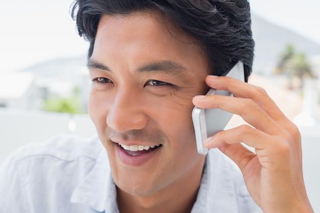 Homme souriant sur appel téléphonique