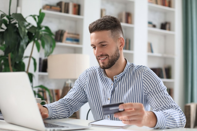 Homme souriant assis au bureau et paie par carte de crédit avec son ordinateur portable.