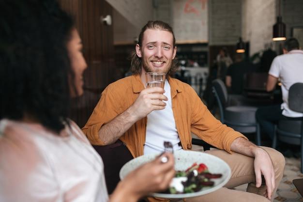 Homme souriant assis au restaurant et parler avec une fille. garçon assis au café avec un verre d'eau à la main