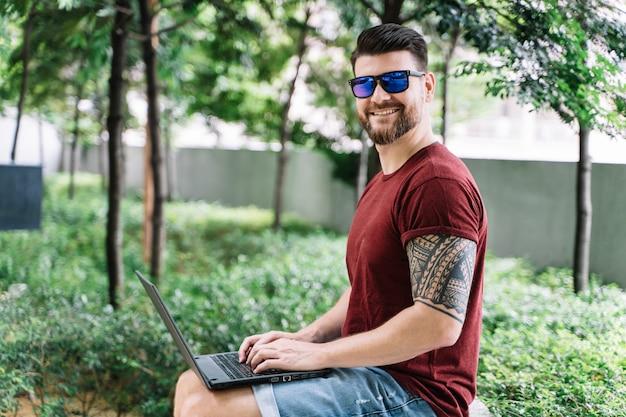Homme souriant et assis sur un banc dans un parc travaillant à distance avec son ordinateur portable