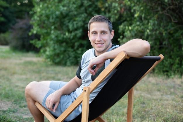 Homme souriant assis sur une chaise longue à bronzer à l'extérieur de la pelouse verte dans le parc personne heureuse à l'extérieur se relaxant sur une chaise longue dans le jardin guy sur un transat le week-end d'été