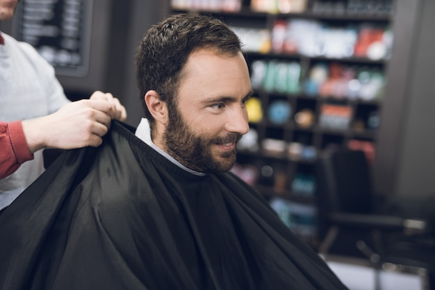 Homme souriant assis dans le salon de coiffure