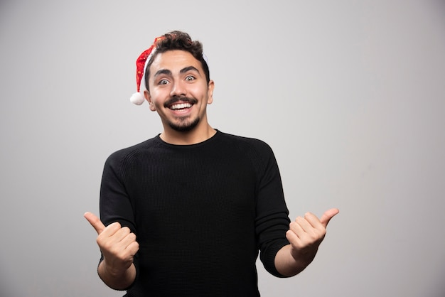 Homme souriant au chapeau du père noël montrant les pouces vers le haut.