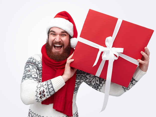 Homme souriant au chapeau de noël tenant une énorme boîte rouge