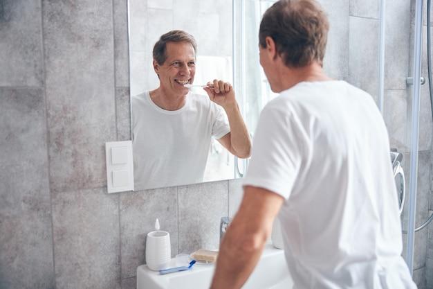 Homme souriant aux cheveux courts se nettoyant les dents devant le miroir de la salle de bain