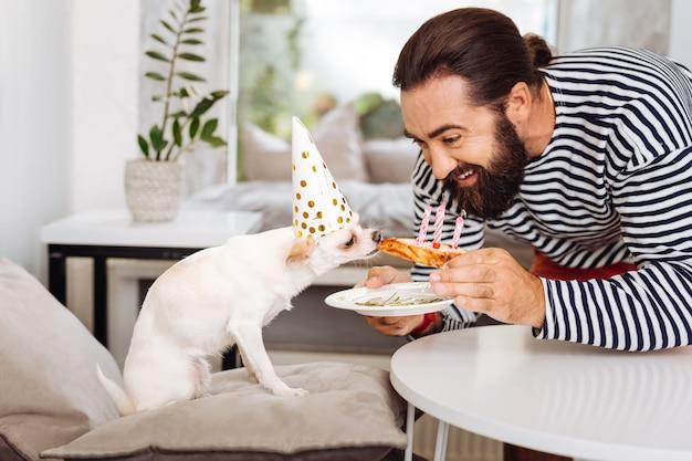 Homme souriant aux cheveux noirs se sentant extrêmement émotif pour célébrer l'anniversaire de son animal de compagnie