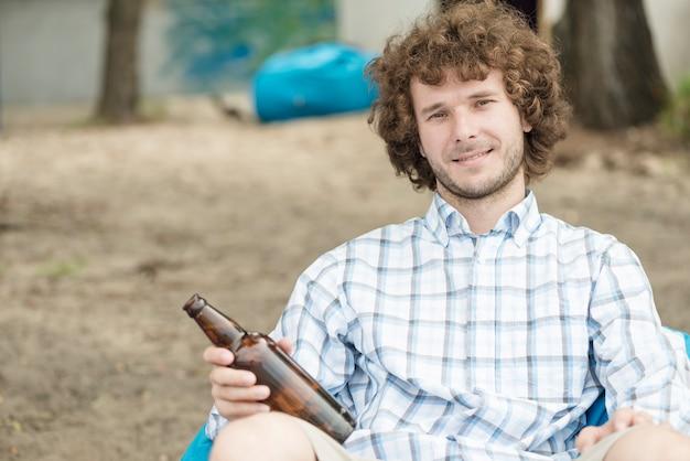 Homme souriant avec de la bière de détente sur la plage