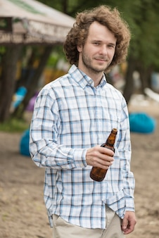 Homme souriant avec de la bière sur la plage