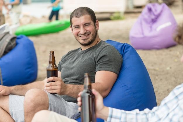 Homme souriant, boire de la bière chez un ami