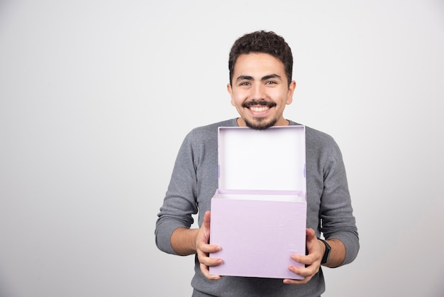 Homme souriant avec une boîte violette ouverte sur un mur blanc.