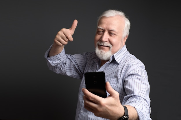 Homme souriant de bonne humeur fait selfie sur un téléphone mobile intelligent sur un fond gris