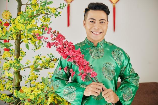 Homme souriant avec des branches de pêche en fleurs