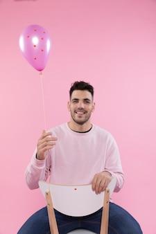 Homme souriant sur une chaise tenant un ballon violet